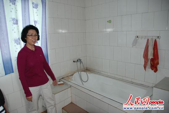 中国妇女发展基金会秘书长秦察看杨彩焕家浴室